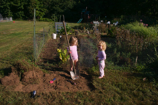 Charlotte and Bea help excavate the spot for the raised bed and mini hoop house.