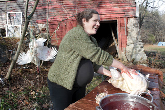 Margaret, extremely pregnant and 10 days past her due date, cleans one of the turkeys we slaughtered and processed today.